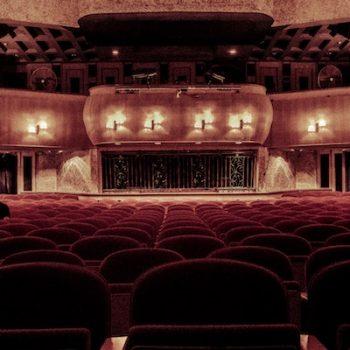 Ein Kinosaal mit roten Samtsitzen und barocken Verzierungen. Links sitzt ein einzelner junger Mann in Schwarz.